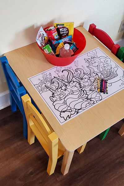 Desk with bowl of treats and coloring page with crayons